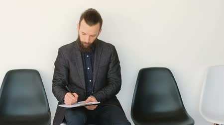 kandidát : Bearded hipster in black suit. Business meeting employment. Job applicant sitting filling in form putting ticks signing.