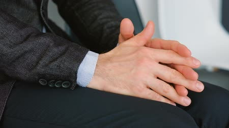 subordinate : Office man apprehension. Nervous clenching hands closeup. Guy in suit rubbing palms fingers together tapping on knees.