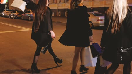 favori : Black Friday. Night shopping. Women favorite leisure and hobby. Amused ladies walking down the street with new clothes in bags.
