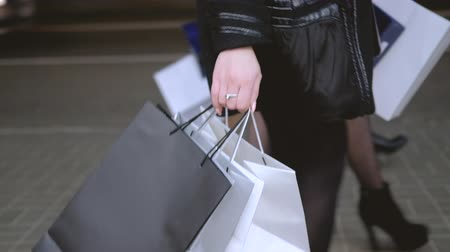 上流階級の : Fashionista lifestyle. Shopping leisure. Girls night. Young female friends walking together down the street with bags. 動画素材