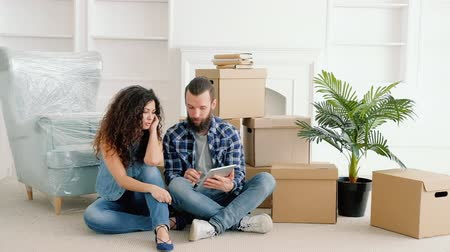 szállás : Young couple having rest after moving stuff to their own house, sitting on floor, buying furniture online for new home.