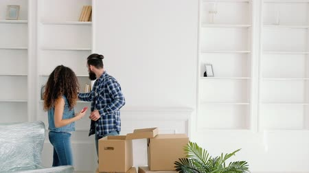 coisas : Moving home. Young couple unpacking boxes with stuff, creating cozy interior design. Stock Footage