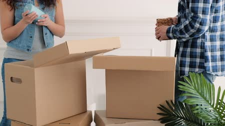 mozgás : Moving home. Young couple unpacking boxes with stuff, creating cozy interior design. Stock mozgókép