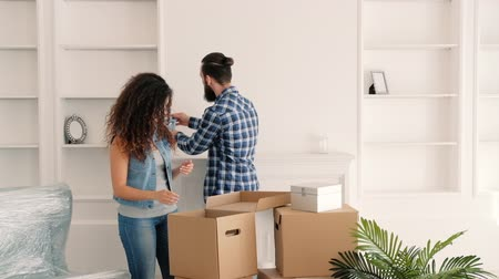 tágas : Moving home. Happy young couple unpacking boxes with decorative stuff, creating cozy atmosphere.