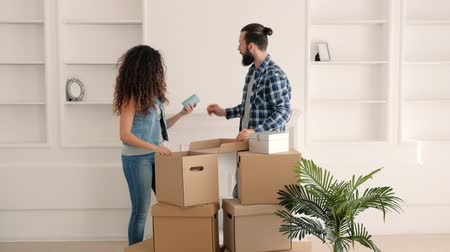 materiaŁ : Moving home. Happy young couple enjoying decorating room in their new modern apartment.