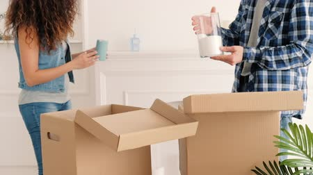 szállás : Moving home. Young couple unpacking candles to decorate room in their new modern apartment. Stock mozgókép