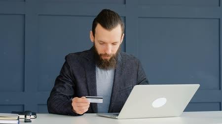 дебет : Online payment. Money transaction and orders. Man typing data from his credit card on the laptop.
