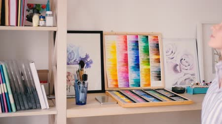 taslakkitabım : Neatly organized tidy artist studio. Artworks supplies around. Young blonde female taking watercolor sketchpad from shelf. Stok Video
