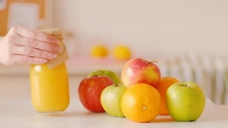 апельсины : Slider shot of apples oranges pile. Woman hand placing glass bottle of smoothie next to fruit. Healthy dieting eating detox.