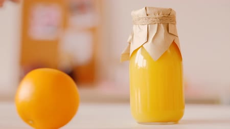прессованный : Glass bottle of fresh juice smoothie on kitchen table closeup. Orange rolling. Healthy nutrition fitness cleansing products.