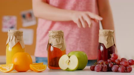 tápanyagok : Woman choosing bottle of fresh fruit juice using counting out game. Taking apple smoothie leaving. Healthy dieting eating. Stock mozgókép