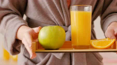 balanced : Healthy breakfast. Morning habits. Fresh fruit diet. Vegan lifestyle. Woman serving orange slices, apple and juice on tray. Stock Footage