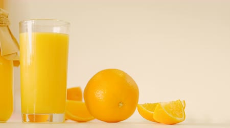 balanced : Balanced nutrition. Healthy lifestyle. Arrangement of orange, fruit slices, fresh juice in glass, bottle. Organic vitamin drink. Stock Footage