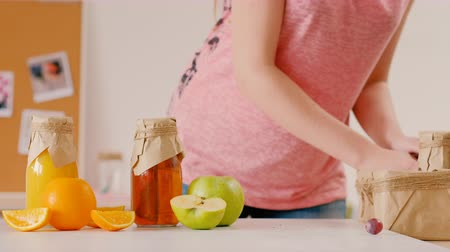 balanced : Vegetarian picnic. Healthy nutrition. Woman packing organic fruit and rustic bottles with natural vitamin drink in paper box. Stock Footage