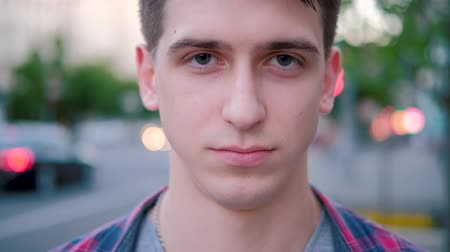 tehdit : Serious confident menacing or threatening look with a smile in the end. Young man closeup portrait.