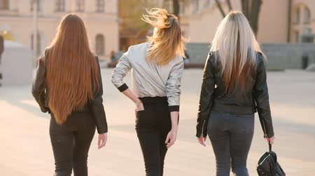 feminist : Female friends team. Back view of young ladies walking confidently down the city street.