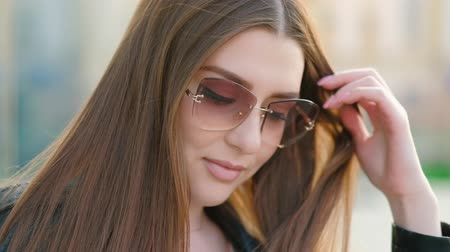 feminist : Alluring woman flirting. Gorgeous brunette lady in sunglasses playing with her beautiful long hair at sunset. Blur background. Stock Footage