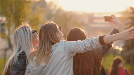 зависать : Young ladies enjoying evening, happy spending time together, taking selfie in city park at sunset.
