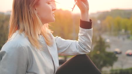 feminist : Beautiful evening. Blonde young lady enjoying sunset in city park. Peaceful facial expression. Blur background.
