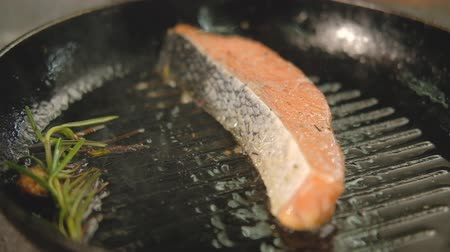 segurelha : Restaurant fish meal cooking. Piece of salmon or trout fillet frying on grilled pan.