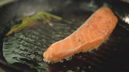 filet : Fish cooking recipe. Piece of salmon or trout fillet frying on grilled pan.