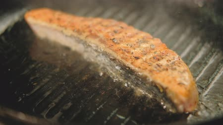 segurelha : Food cooking. Fish frying. Piece of salmon or trout steak with spices on grilled pan.