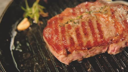 sirloin : Pork chop roasting in grilled pan closeup. Chef juicing red meat steak on frying pan.