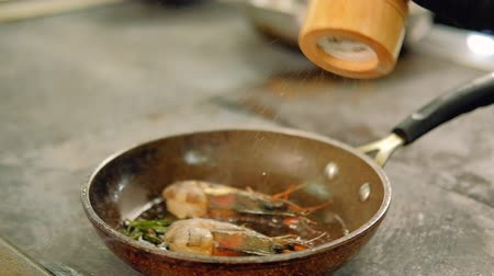 seafood recipe : Seafood meal recipe. Seasoning and spicing food. Chef adding pepper to shrimp in frying pan