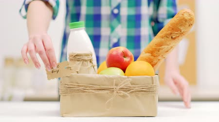джут : Local buy organic products. Selection of goods from farmers market. Milk fruit and french bread in a craft box Стоковые видеозаписи