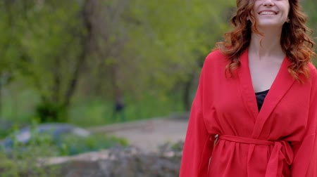 coquettish : Confident smiling woman walking outside. Red outfit and curly ginger hair