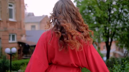 весна : Female beauty. Relaxed happy woman walking and turning around laughing. Curly ginger red hair.