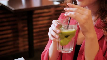 tonikum : Woman drinking fresh lemon cocktail. Lifestyle and carefree leisure.