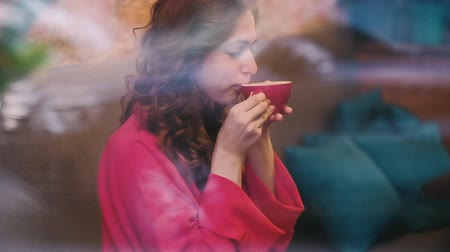 zázvor : Woman enjoying cup of coffee in cafe behind the glass. Cute girl drinking hot latte or cappuccino in a red mug.