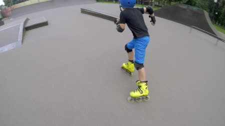 inline : Sporty kids leisure. Boy on roller skating on the ramp in the park