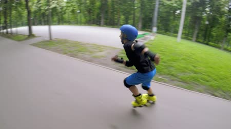 inline skating : Kids fun cardio training. Fast inline skating. Boy speeding through the park.