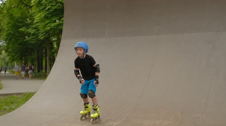 inline skating : Kids sports and athletic development. Roller boy training on the ramp.
