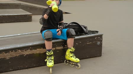 hidrasyon : Hydratation during active kids leisure. Roller boy drinking water from a sport bottle Stok Video