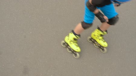 inline skating : Rollerblading training. Boy in blue helmet and yellow rollers skating on the asphalt