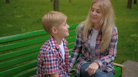 dizer : Family communication. Mom and son chatting. Relaxed leisure on a bench in park.