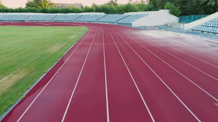 トラック : Flying over running track at stadium. Reaching goal and winning. Sport motivation