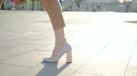 follow shot : Legs walking in the city. Tracking shot of stylish woman feet in white heeled shoes.