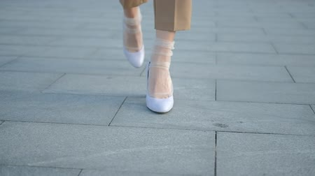 calças : Legs walking in the city. Confidence and style on heels. Female feet in trendy shoes and socks