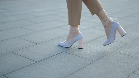calças : Legs walking. Urban fashion. Tracking shot of stylish woman feet in white heeled shoes.