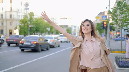 бежевый : Late in big city calling for a cab. Woman flaging taxi standing near road waving her hand Стоковые видеозаписи