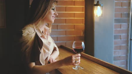 timeout : Enjoying glass of wine. Relaxed woman drinking alcohol in cafe looking out window