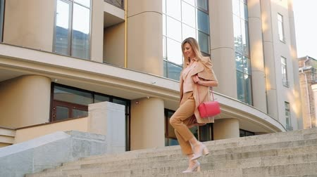 бежевый : Business rushing lifestyle. Woman running down the stairs in the city.
