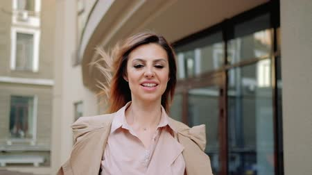 бежевый : Sudden rush. Excited woman smiling and starting to run towards camera. Worried facial expression Стоковые видеозаписи