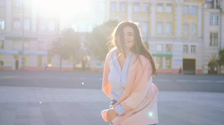 восхищенный : Body positive freedom. Joyful curvy female dancing in the street. Urban sunlight flares