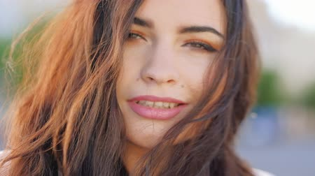 coquettish : Flirty woman portrait. Smiling beautiful female brunette playing with her hair. Closeup portrait Stock Footage