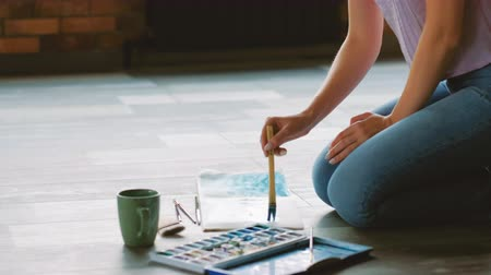 műalkotás : Artist lifestyle. Painter creating watercolor artwork sitting on the floor